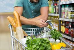 man shopping in supermarket with phone